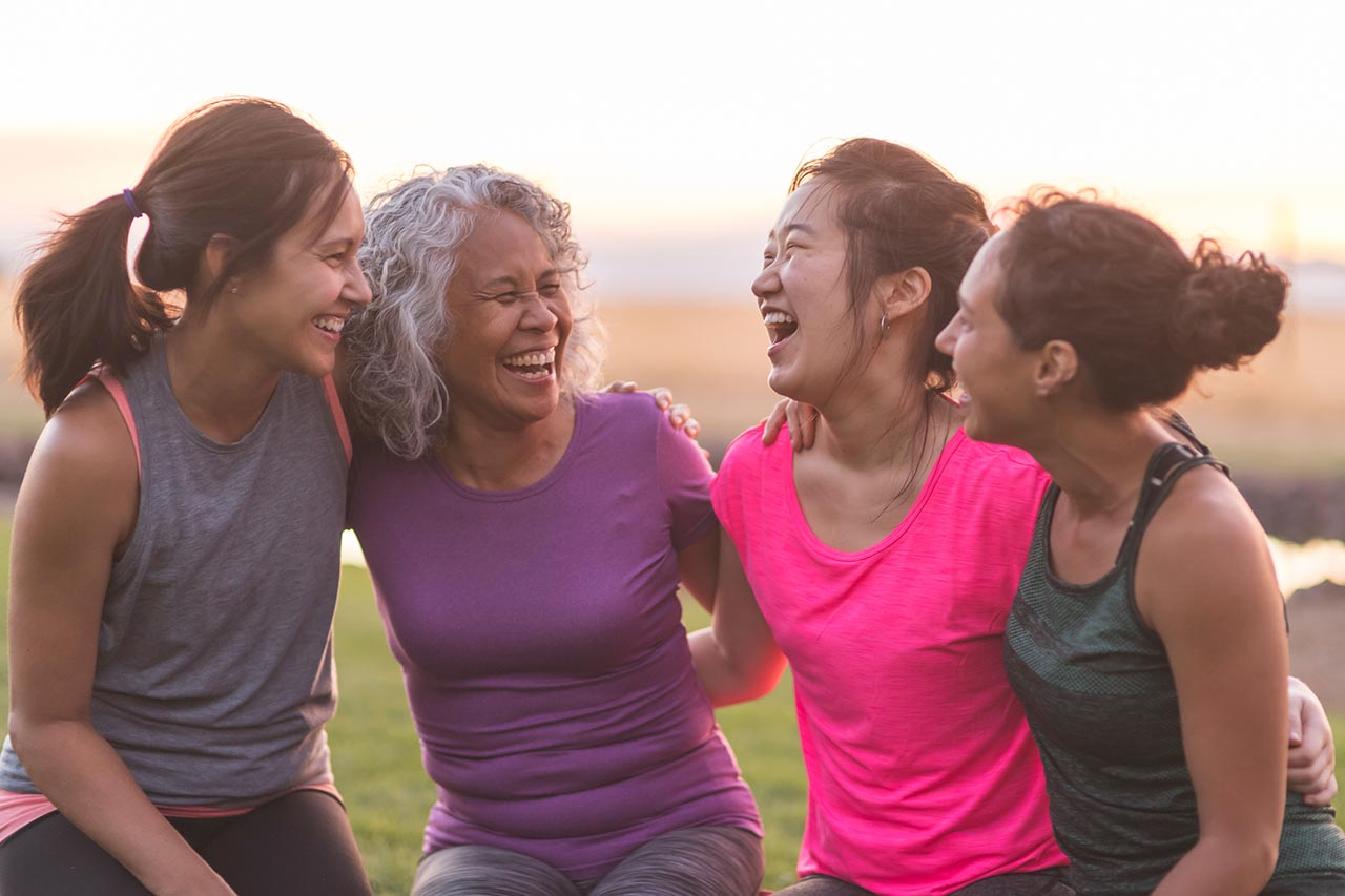 Four ethnic women of varying ages hug each other and laugh heartily after an intense workout together outside on a summer evening.